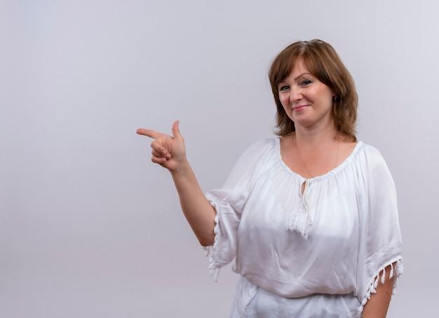 Sonriente mujer de mediana edad apuntando con el dedo al lado izquierdo en la pared blanca aislada