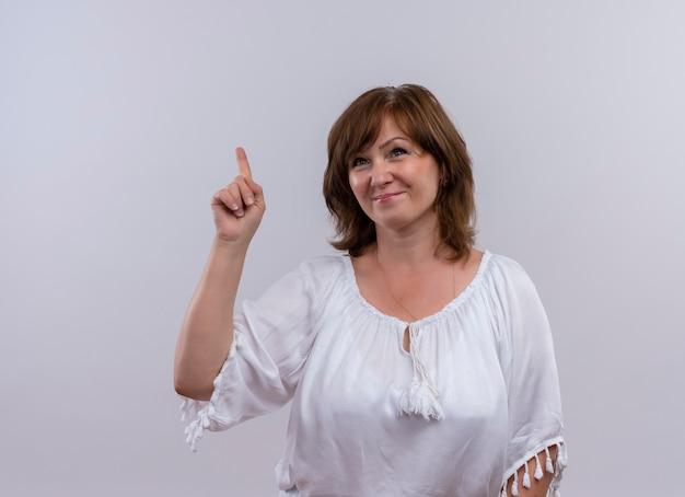Sonriente mujer de mediana edad apuntando con el dedo hacia arriba en la pared blanca aislada