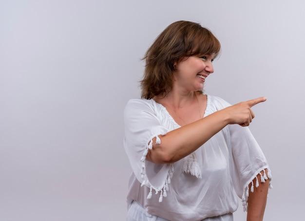 Sonriente mujer de mediana edad apuntando con el dedo en la pared blanca aislada