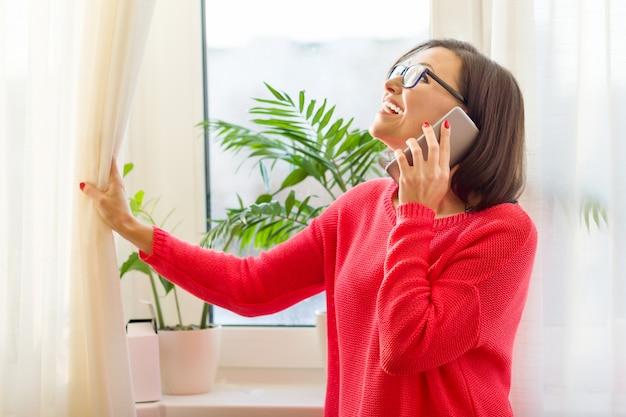 Sonriente mujer de mediana edad hablando por teléfono