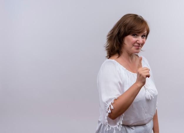 Sonriente mujer de mediana edad mostrando el dedo en la pared blanca aislada