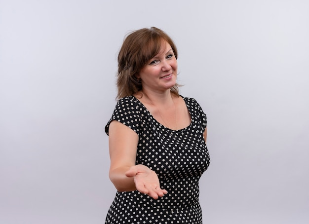 Sonriente mujer de mediana edad mostrando la mano vacía en la pared blanca aislada