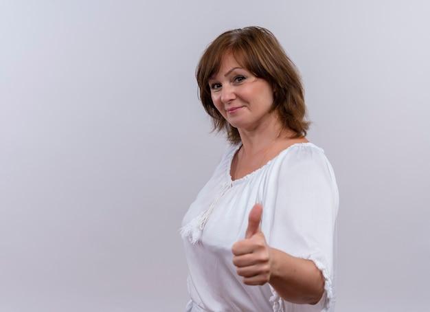 Sonriente mujer de mediana edad mostrando el pulgar hacia arriba en la pared blanca aislada