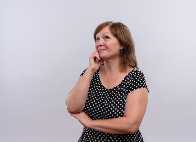 Sonriente mujer de mediana edad poniendo la mano en la barbilla en la pared blanca aislada con espacio de copia