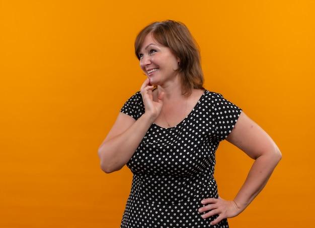 Sonriente mujer de mediana edad poniendo las manos en el pecho y la cintura en la pared naranja aislada con espacio de copia