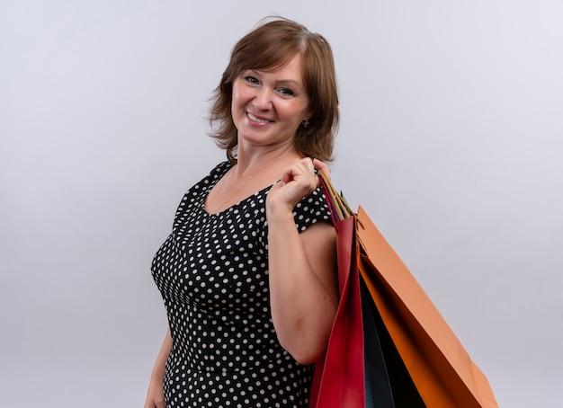 Sonriente mujer de mediana edad sosteniendo bolsas de cartón en la pared blanca aislada