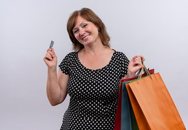 Sonriente mujer de mediana edad sosteniendo bolsas de cartón y tarjetas en la pared blanca aislada