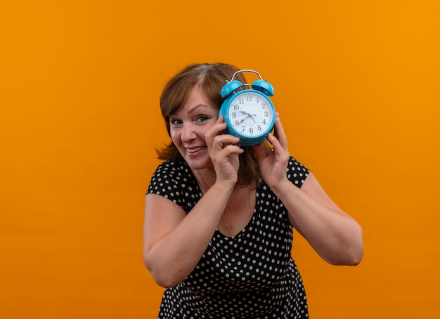 Sonriente mujer de mediana edad sosteniendo el despertador y mirando detrás de él en la pared naranja aislada con espacio de copia