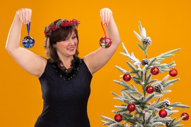 Sonriente mujer de mediana edad vistiendo guirnalda de cabeza de navidad y guirnalda de oropel alrededor del cuello de pie cerca del árbol de navidad decorado