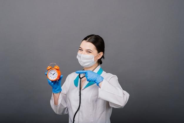 Sonriente mujer médico en máscara apuntando en el reloj, tiempo de vacunación