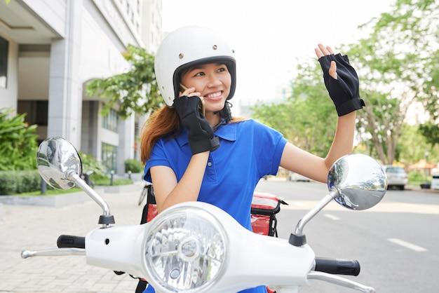 Sonriente mujer mensajero en scooter