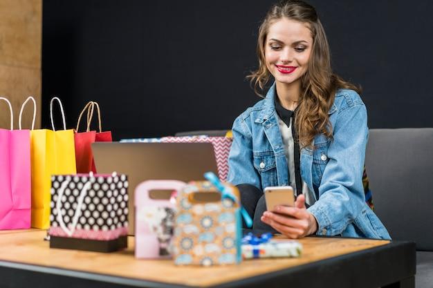 Sonriente mujer de moda sentada en casa con bolsas de compras; portátil y teléfono inteligente