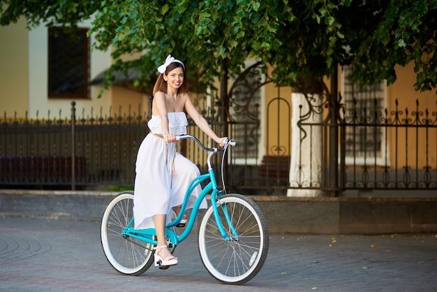 Sonriente mujer montando una bicicleta en una calle soleada de la ciudad