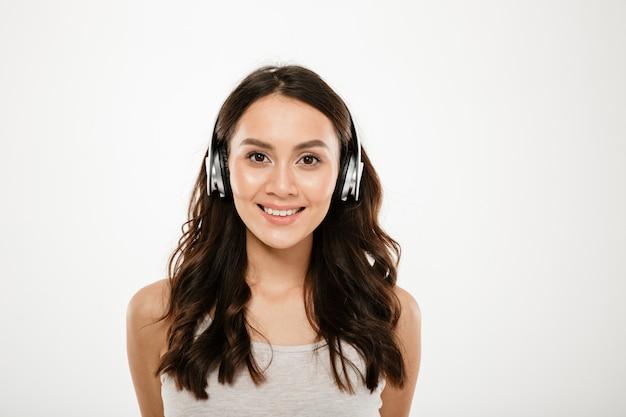 Sonriente mujer morena en auriculares escuchando música y mirando a la cámara sobre gris