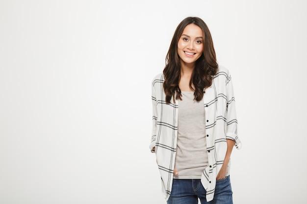 Sonriente mujer morena en camisa posando con los brazos en los bolsillos y mirando a la cámara sobre gris Foto gratis