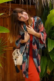 Sonriente mujer morena despreocupada en elegante traje de verano disfrutando de vacaciones en resort de lujo. jardín exótico con plantas tropicales.