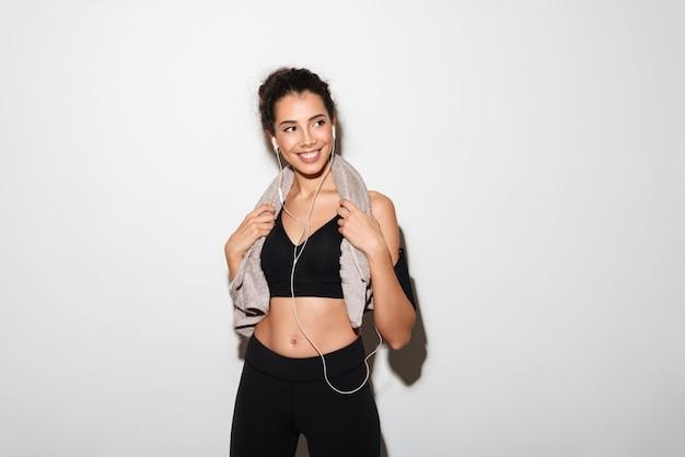 Sonriente mujer morena fitness rizada con toalla escuchando música