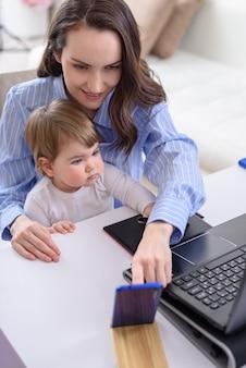 Sonriente mujer morena con niño sentado en el portátil