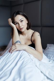 Sonriente mujer morena de pelo largo en cama blanca en suave luz de la mañana bajo el edredón