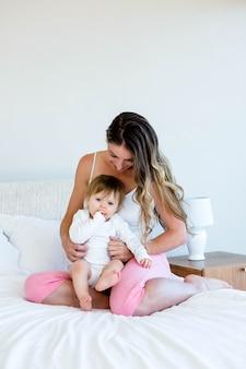 Sonriente mujer morena, sentada en su cama, sosteniendo a un lindo bebé