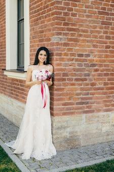 Sonriente mujer morena en vestido de novia blanco largo y hermoso, tiene ramo, se encuentra cerca del edificio de ladrillo