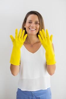 Sonriente mujer mostrando las manos en guantes de goma