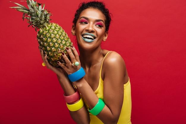 Sonriente mujer mulata con maquillaje de moda en camisa amarilla disfrutando de vitaminas naturales sosteniendo en manos piña madura fresca aislada, sobre pared roja