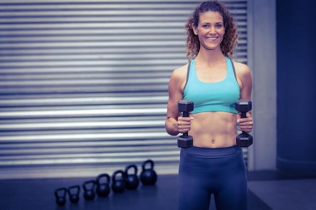 Sonriente mujer muscular levantando pesas