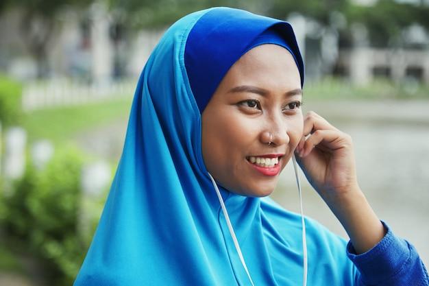 Sonriente mujer musulmana enchufar auriculares en la calle