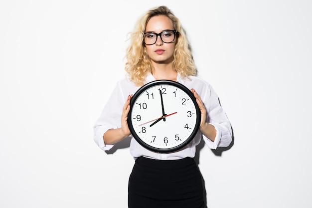 Sonriente mujer de negocios en anteojos con reloj sobre pared gris