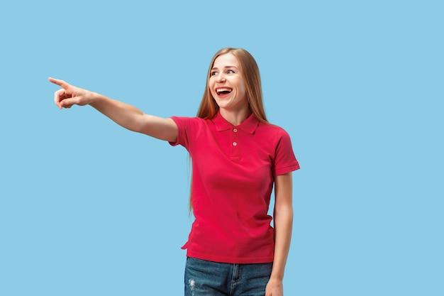 Sonriente mujer de negocios apunta, te quiero, retrato de detalle de media longitud sobre fondo azul de estudio.