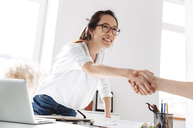 Sonriente mujer de negocios asiática en anteojos en reunión haciendo apretón de manos en la oficina