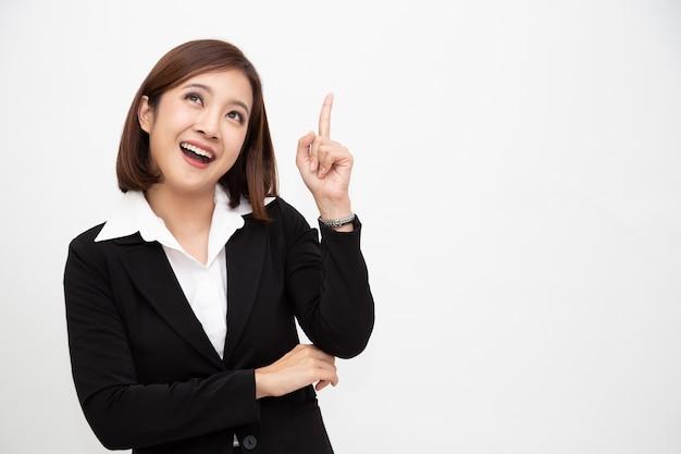 Sonriente mujer de negocios asiática apuntando hacia arriba aislado