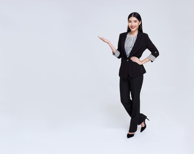 Sonriente mujer de negocios asiática confiada con gesto de introducir aislado sobre fondo gris.