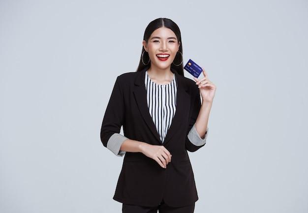 Sonriente mujer de negocios asiática confiada que muestra la tarjeta de crédito aislada sobre fondo gris.
