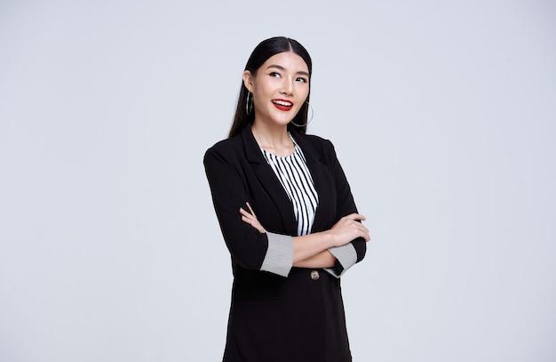 Sonriente mujer de negocios asiática confiada sobre fondo gris.