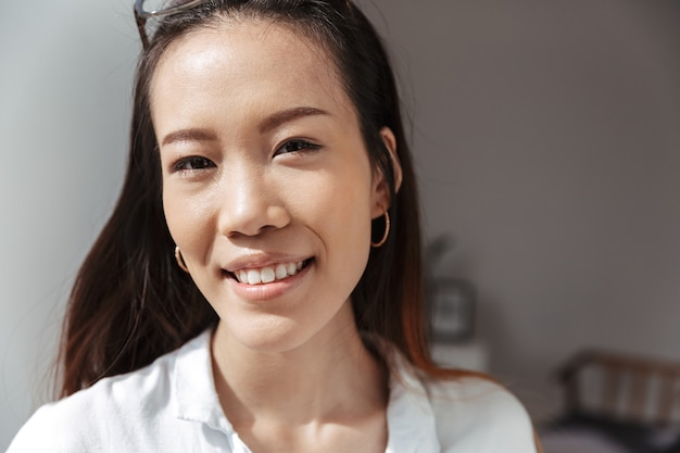 Sonriente mujer de negocios asiática mirando al frente mientras está de pie cerca de la ventana en la oficina