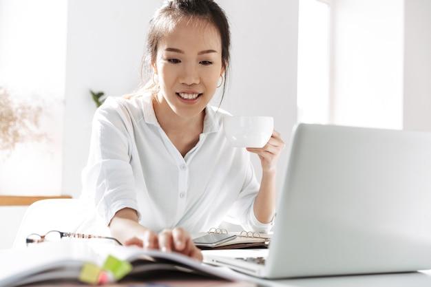 Sonriente mujer de negocios asiática tomando café y usando una computadora portátil mientras está sentado junto a la mesa en la oficina