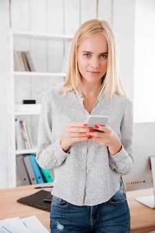 Sonriente mujer de negocios bonita con teléfono móvil en la oficina y mirando al frente