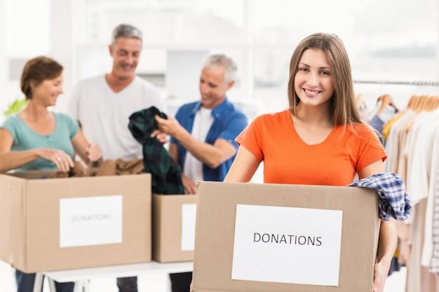 Sonriente mujer de negocios casual con caja de donación