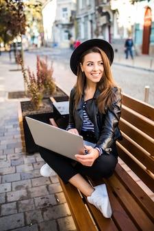 Sonriente mujer de negocios de chica estudiante sentarse en un banco de madera en la ciudad en el parque en día de otoño