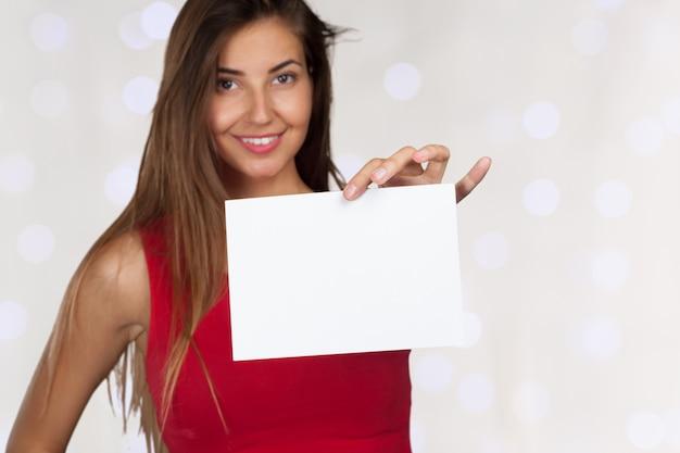 Sonriente mujer de negocios entregando una tarjeta en blanco