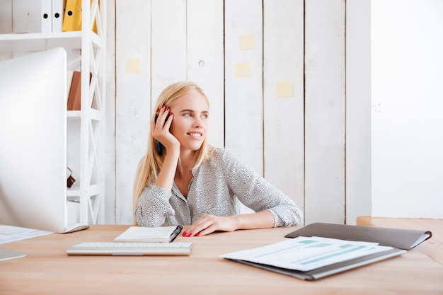 Sonriente mujer de negocios linda sentada en su lugar de trabajo y mirando por la ventana