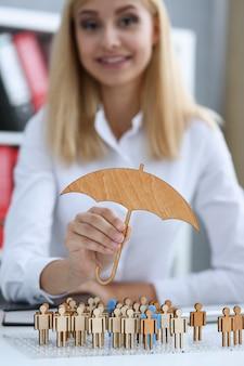 Sonriente mujer de negocios en la mano sostiene un paraguas en miniatura