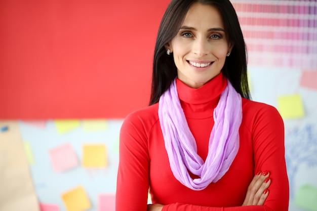 Sonriente mujer de negocios morena en vestido rojo