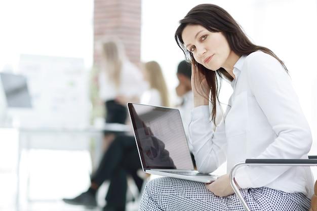 Sonriente mujer de negocios con ordenador portátil en la oficina de fondo borroso.