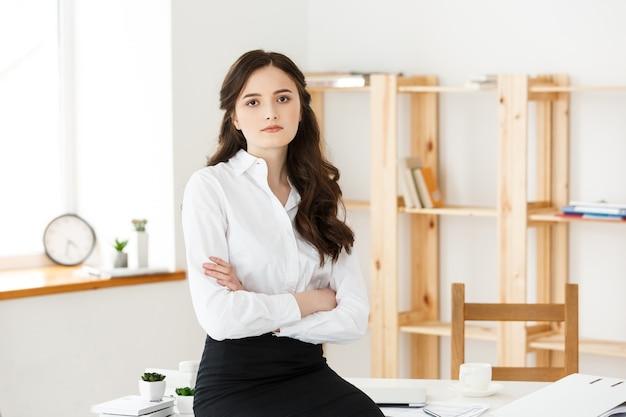 Sonriente mujer de negocios profesional madura con los brazos cruzados sentado en el escritorio en la oficina.