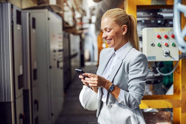 Sonriente mujer de negocios rubia en ropa formal con teléfono inteligente para enviar mensajes de texto mientras está de pie en la planta de energía