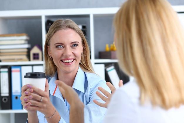 Sonriente mujer de negocios tomando café de un papel