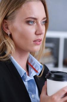 Sonriente mujer de negocios tomando café de una taza de papel
